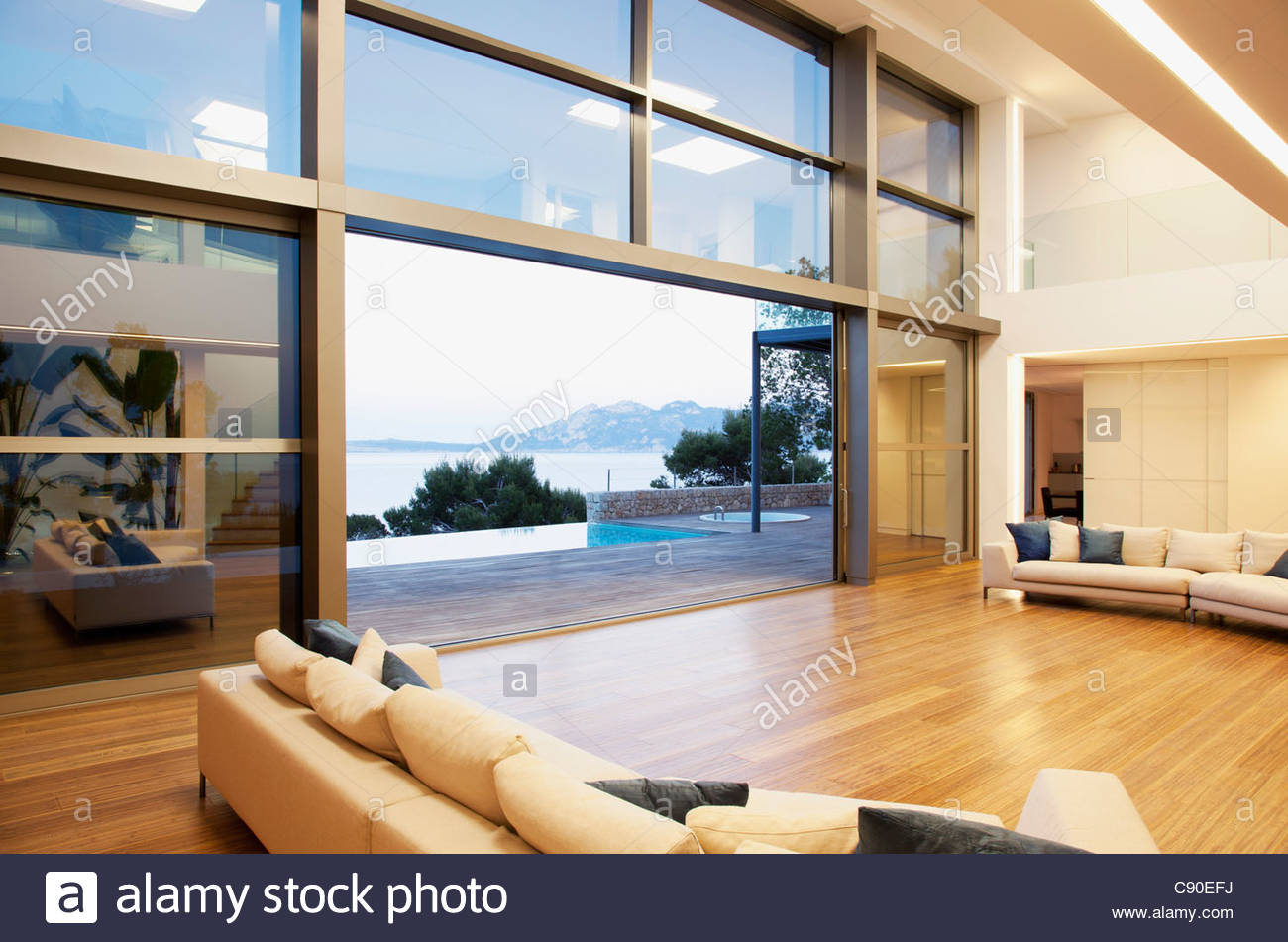 Sofas and sliding doors in open modern house - Stock Image