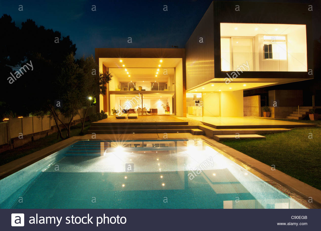 Pool outside modern house at night - Stock Image