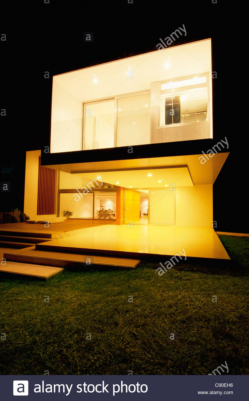 Modern house lit up at night - Stock Image
