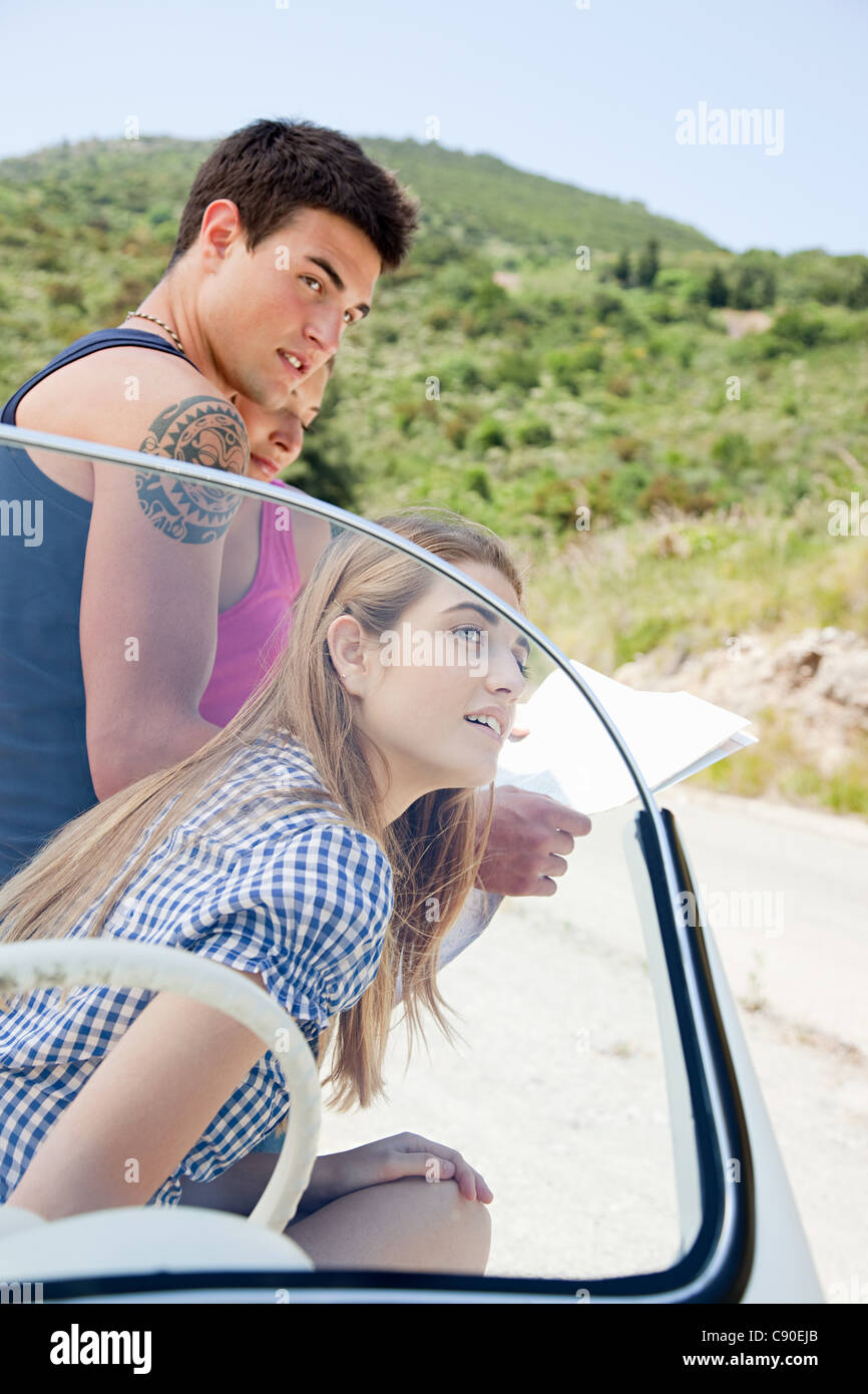 Young people with convertible car looking at map - Stock Image