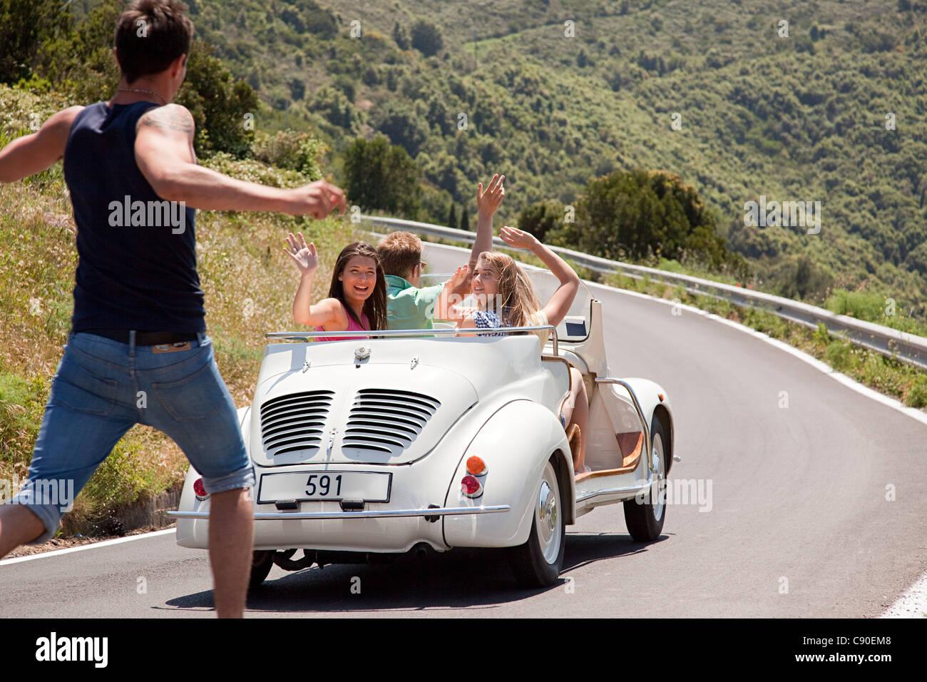 Convertible car driving past hitchhiker - Stock Image