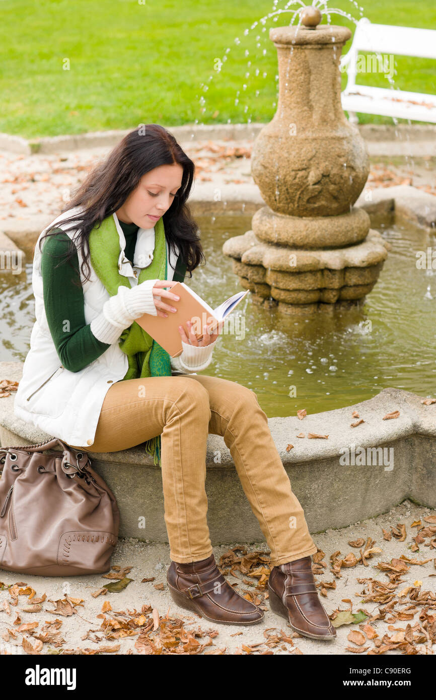 Autumn park young woman reading book sitting on fountain - Stock Image