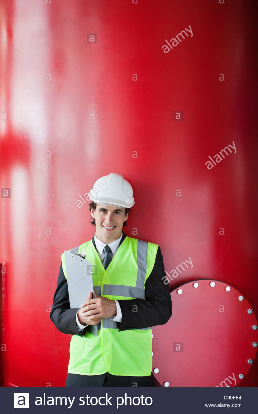 Businessman leaning on tank - Stock Image