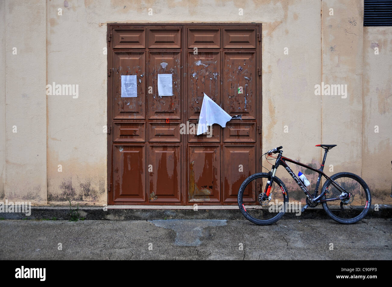 A mountain bike leaning against a gymnasium wall in this pictorial image from Andalusia Spain - Stock Image