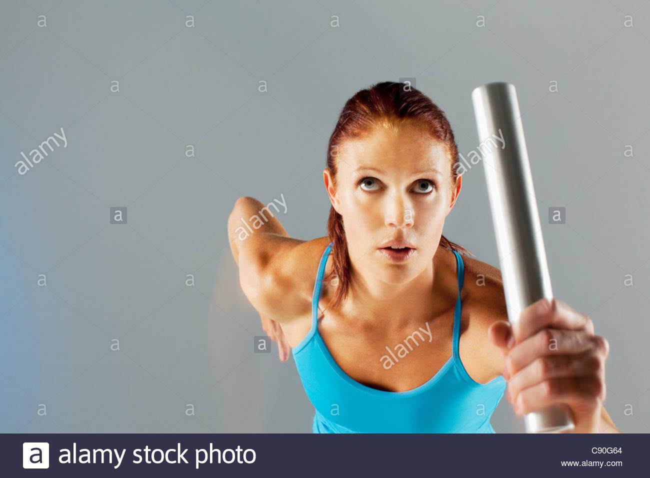 Runner carrying baton - Stock Image