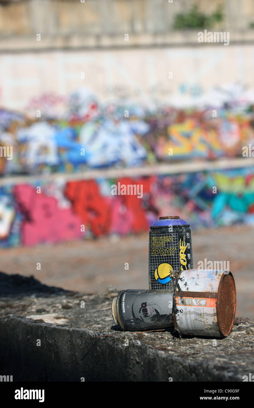 Discarded spray painting cans near a wall of Graffiti - Stock Image