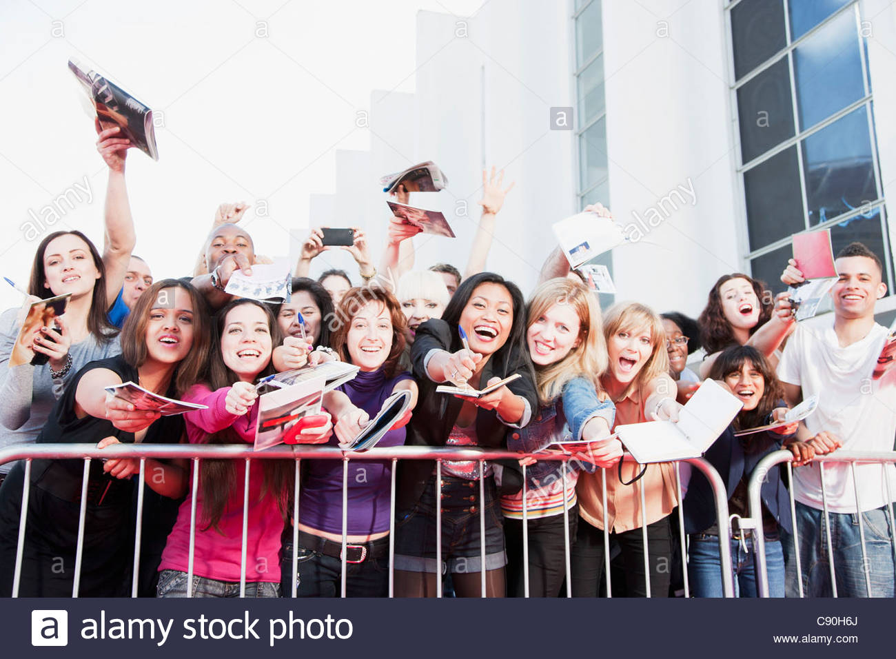 Fans asking for autographs behind barrier - Stock Image