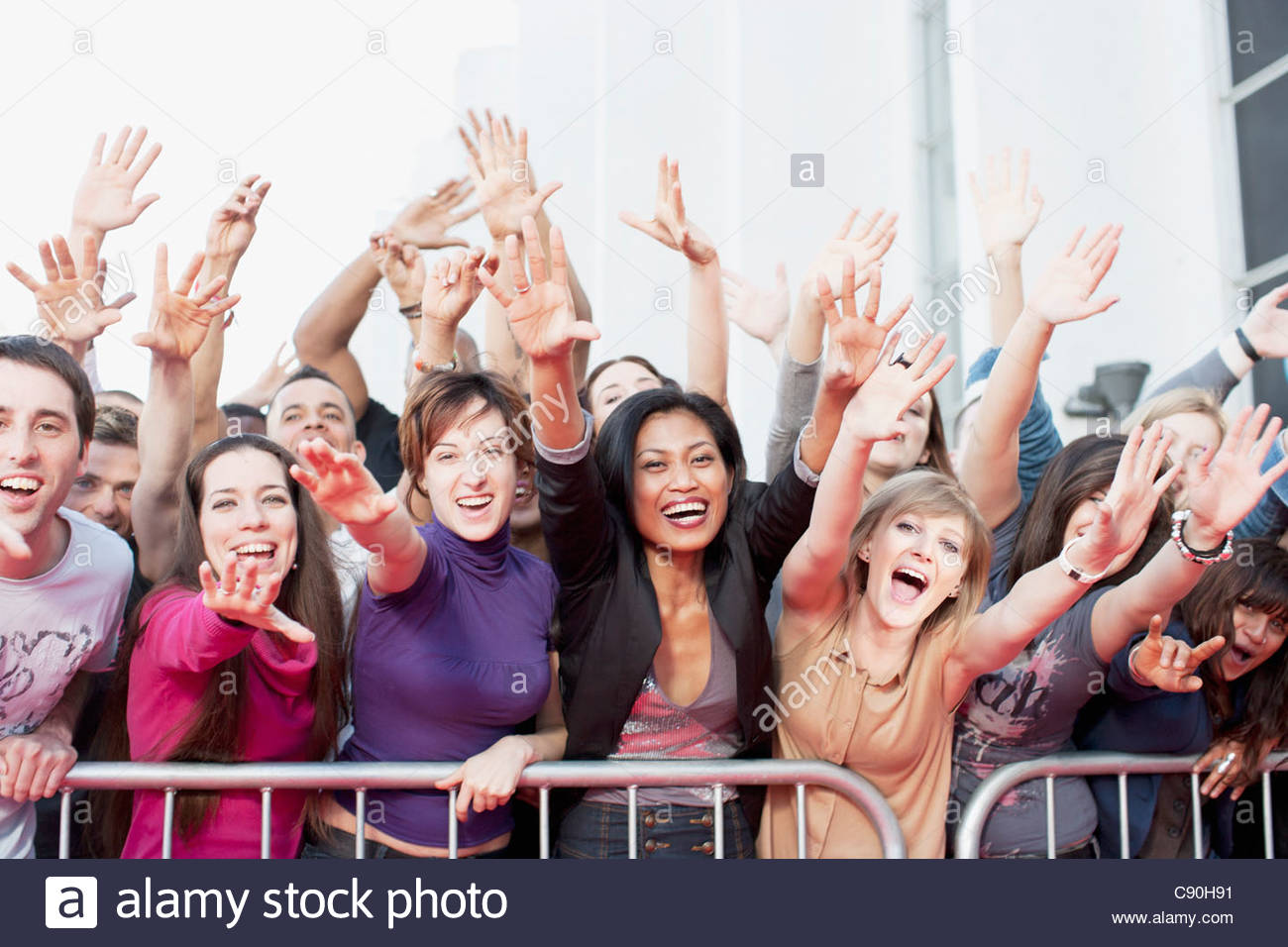 Fans reaching out over barrier - Stock Image