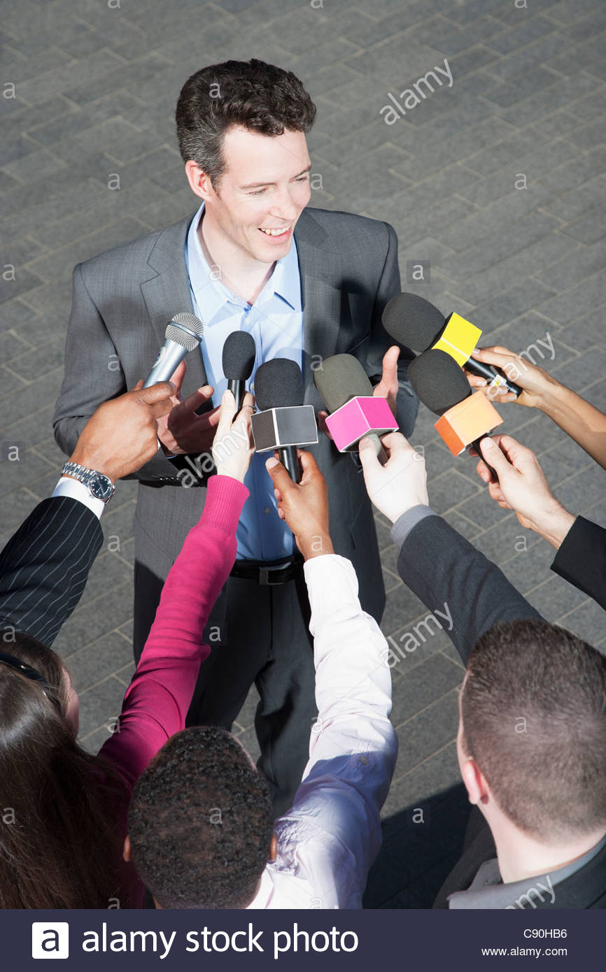 Politician talking into reporters' microphones - Stock Image