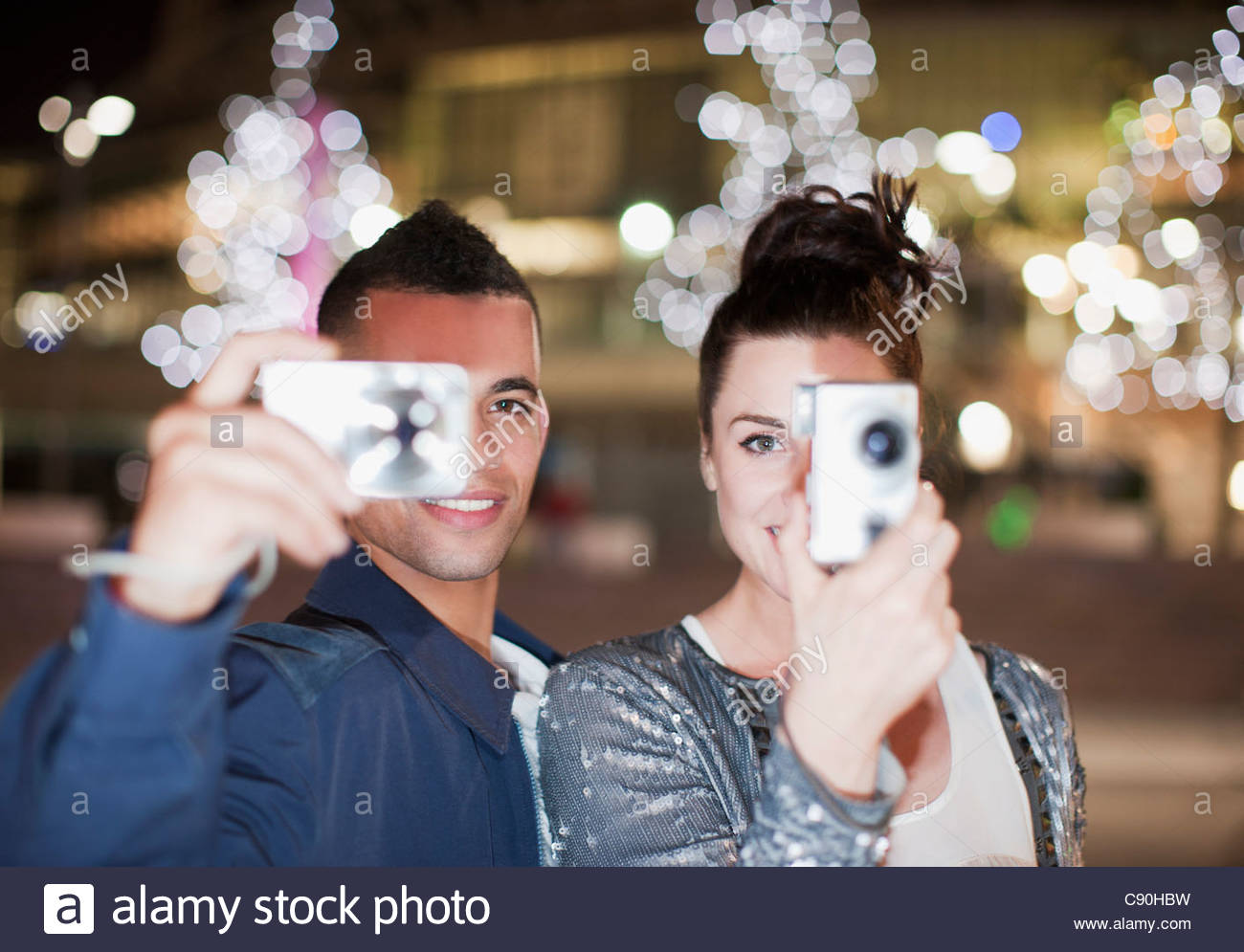 Couple taking pictures on city street at night - Stock Image