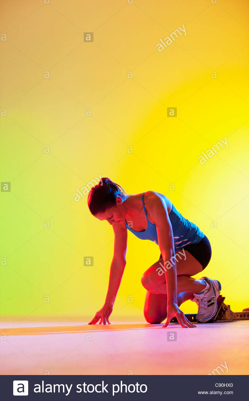 Runner crouched in starting block Stock Photo