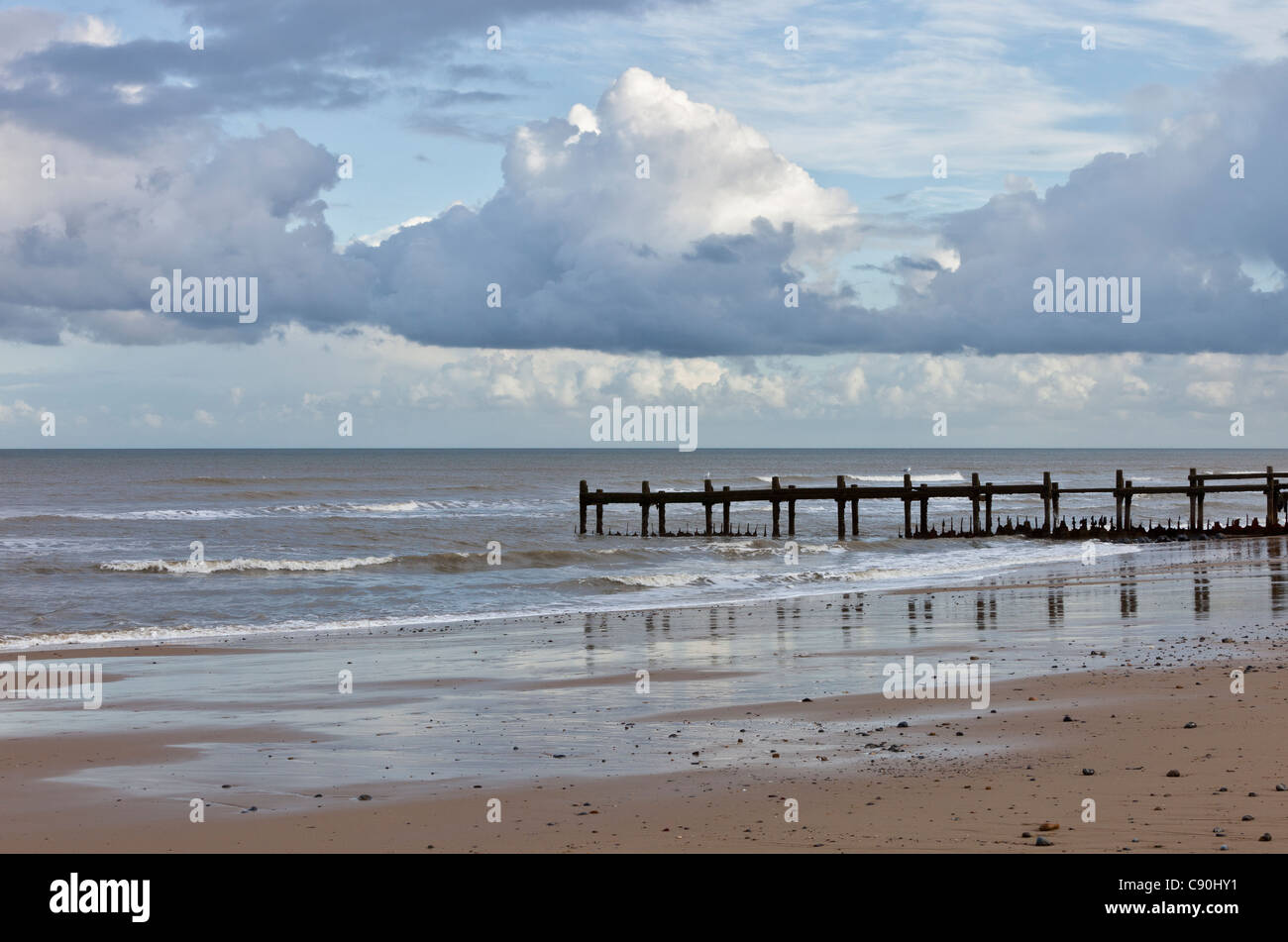 Walcott beach at low tide on the north Norfolk coast with Autumnal shower clouds Stock Photo
