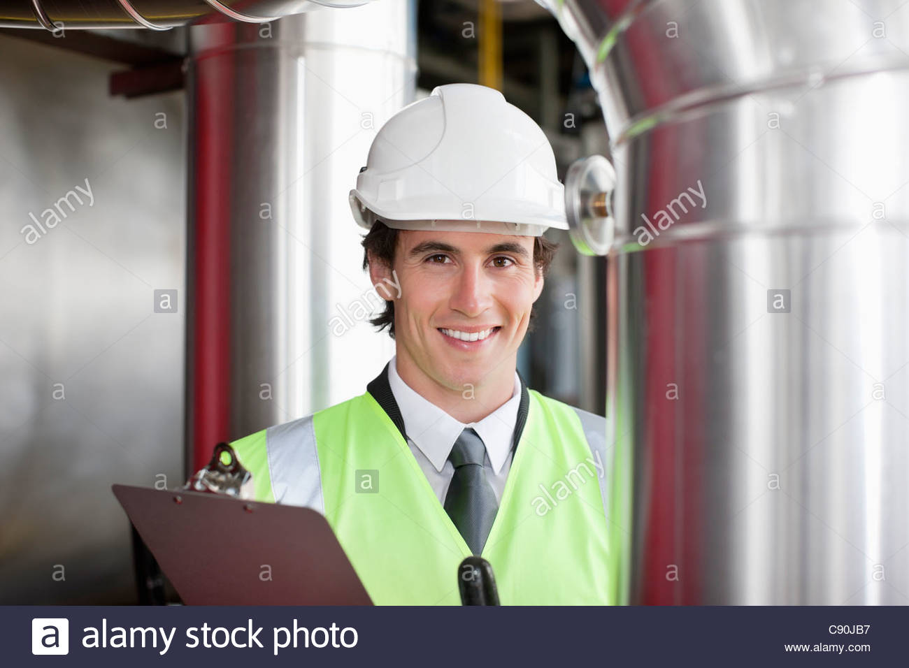 Businessman in safety gear examining pipes - Stock Image