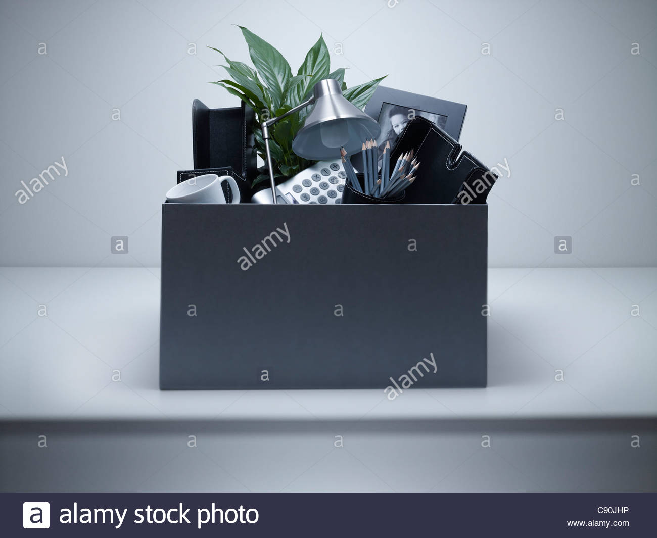 Box packed with desk objects - Stock Image