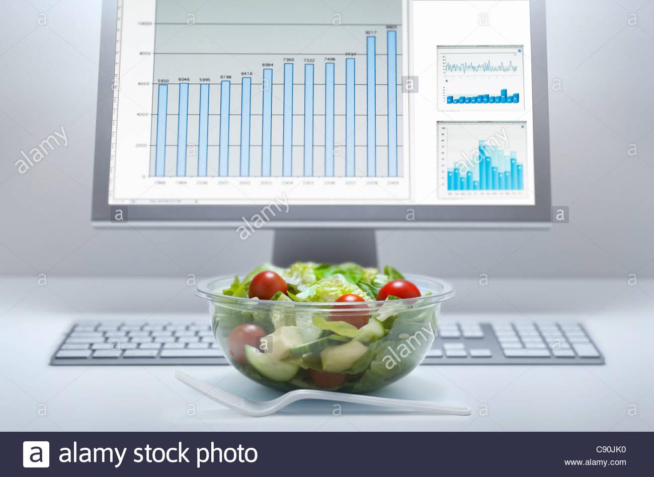 Bowl of salad at computer desk - Stock Image