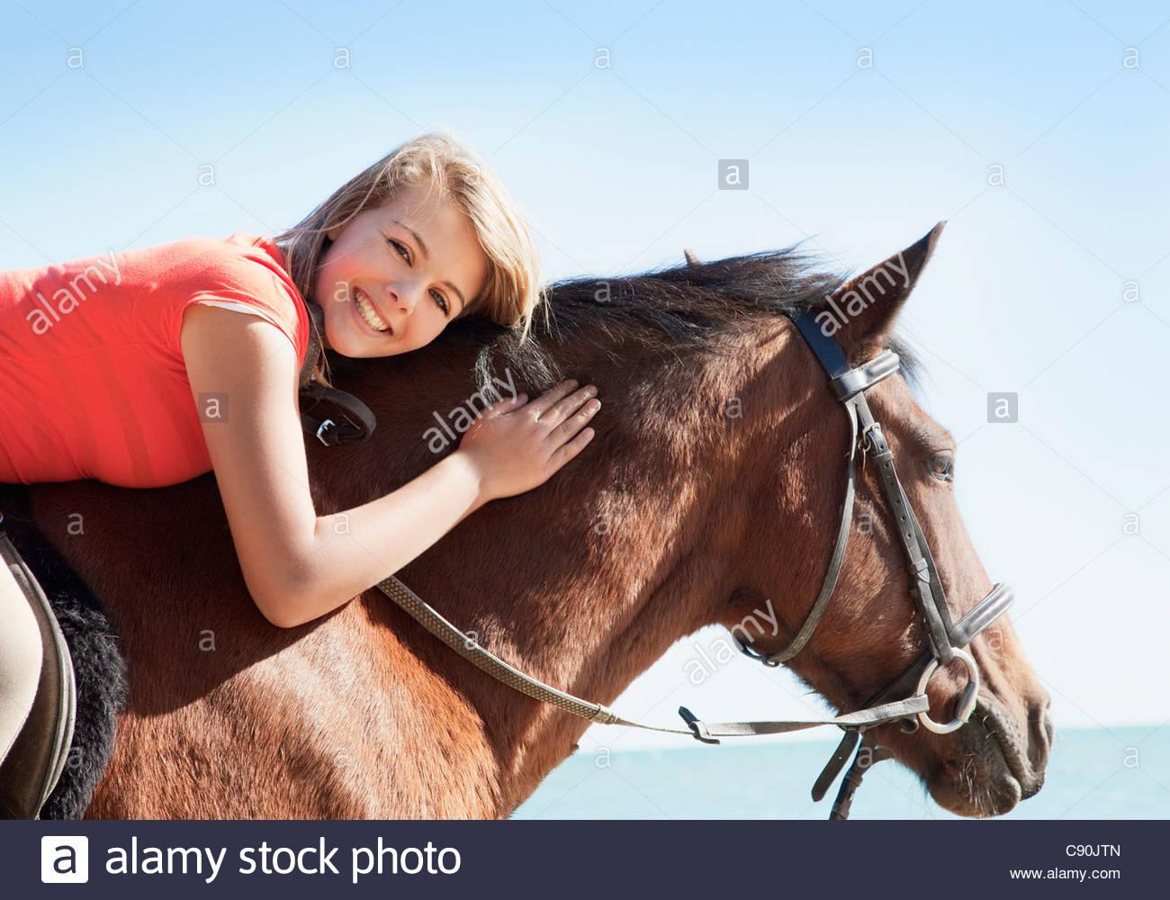 Girl petting horse on beach - Stock Image
