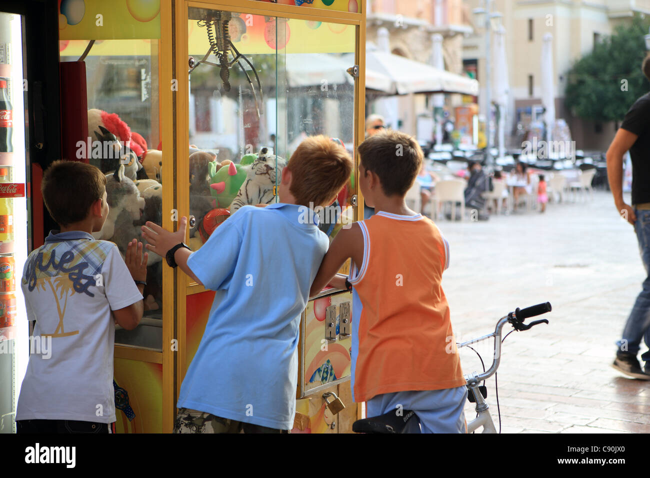 Boys at a soft toy claw crane machine in Syntagmatos Square, Nafplion, Greece - Stock Image