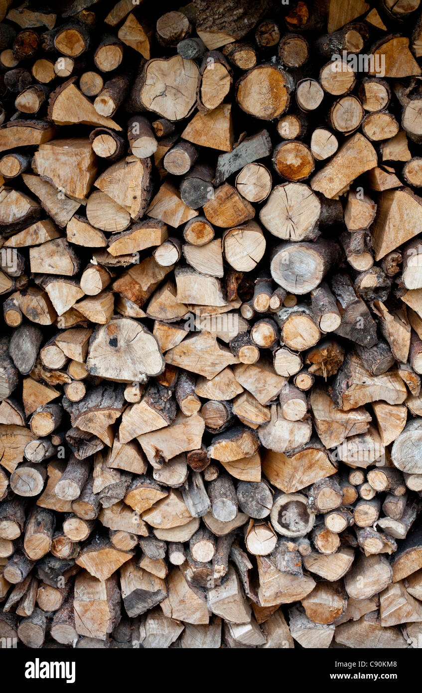 A pile of logs stored ready for use as domestic fuel in a wood burning stove at a home in Shropshire, UK - Stock Image