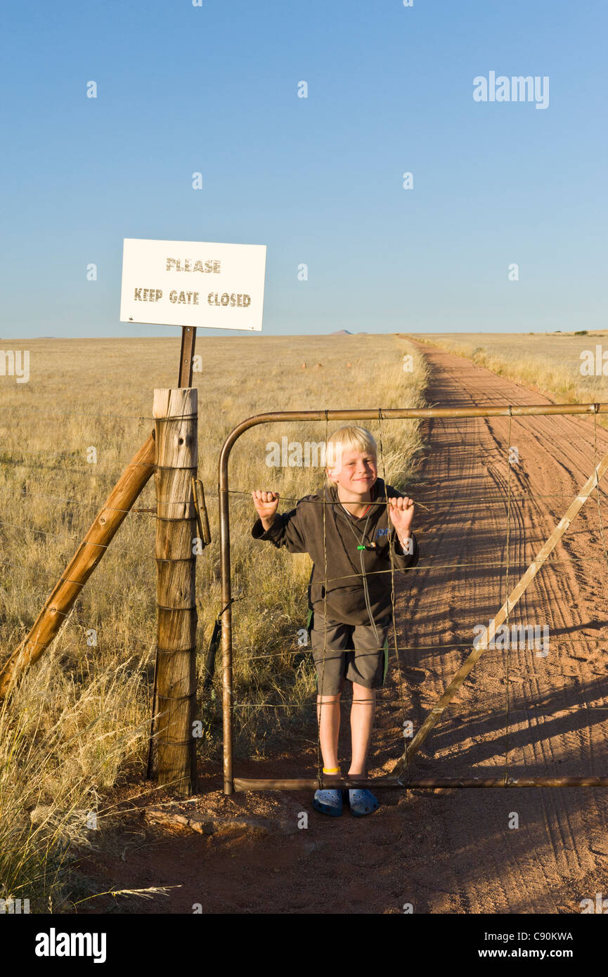 Boy playing with the gate at Koiimasis farm Tiras Mountains Namibia - Stock Image