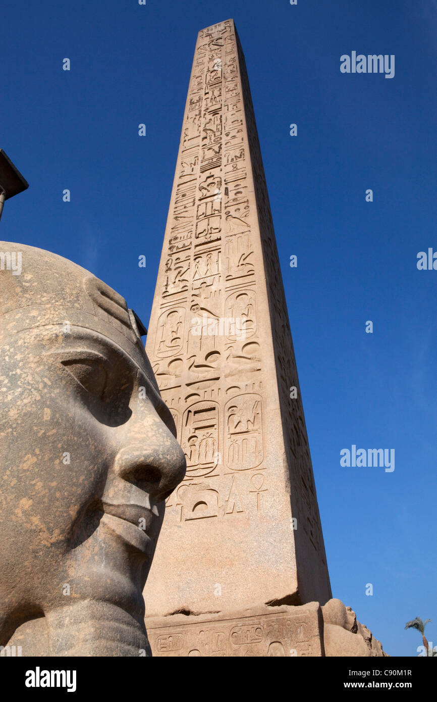 Obelisk and colossal statue of Ramesses II in the entrance area of Luxor Temple, Luxor, Egypt, Africa - Stock Image