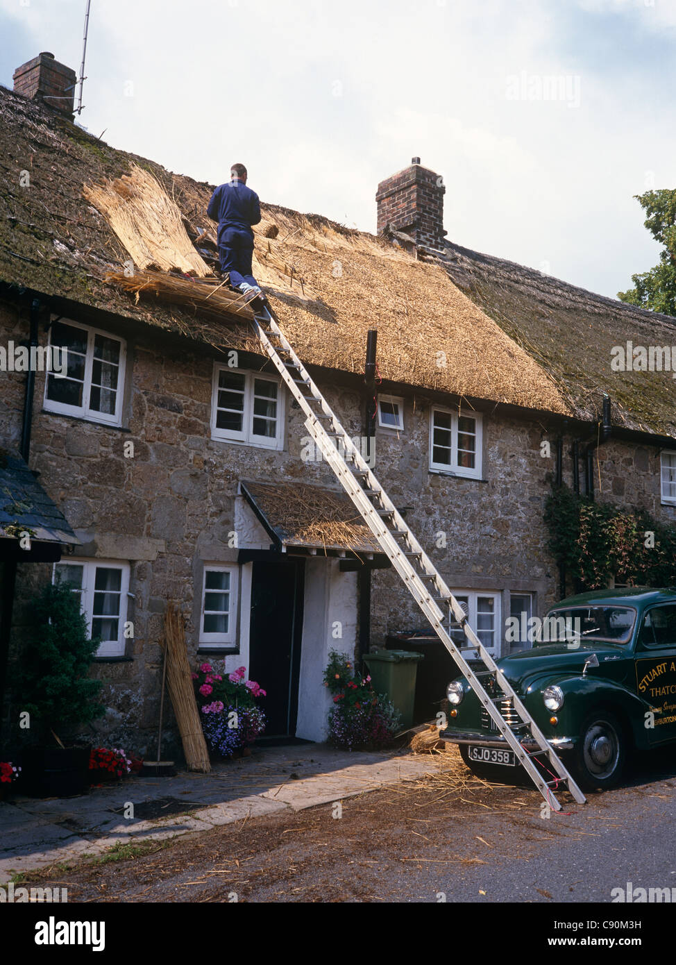 Thatching is a skill Trained craftsmen pack straw and create solid durable and attractive roofs for traditional - Stock Image