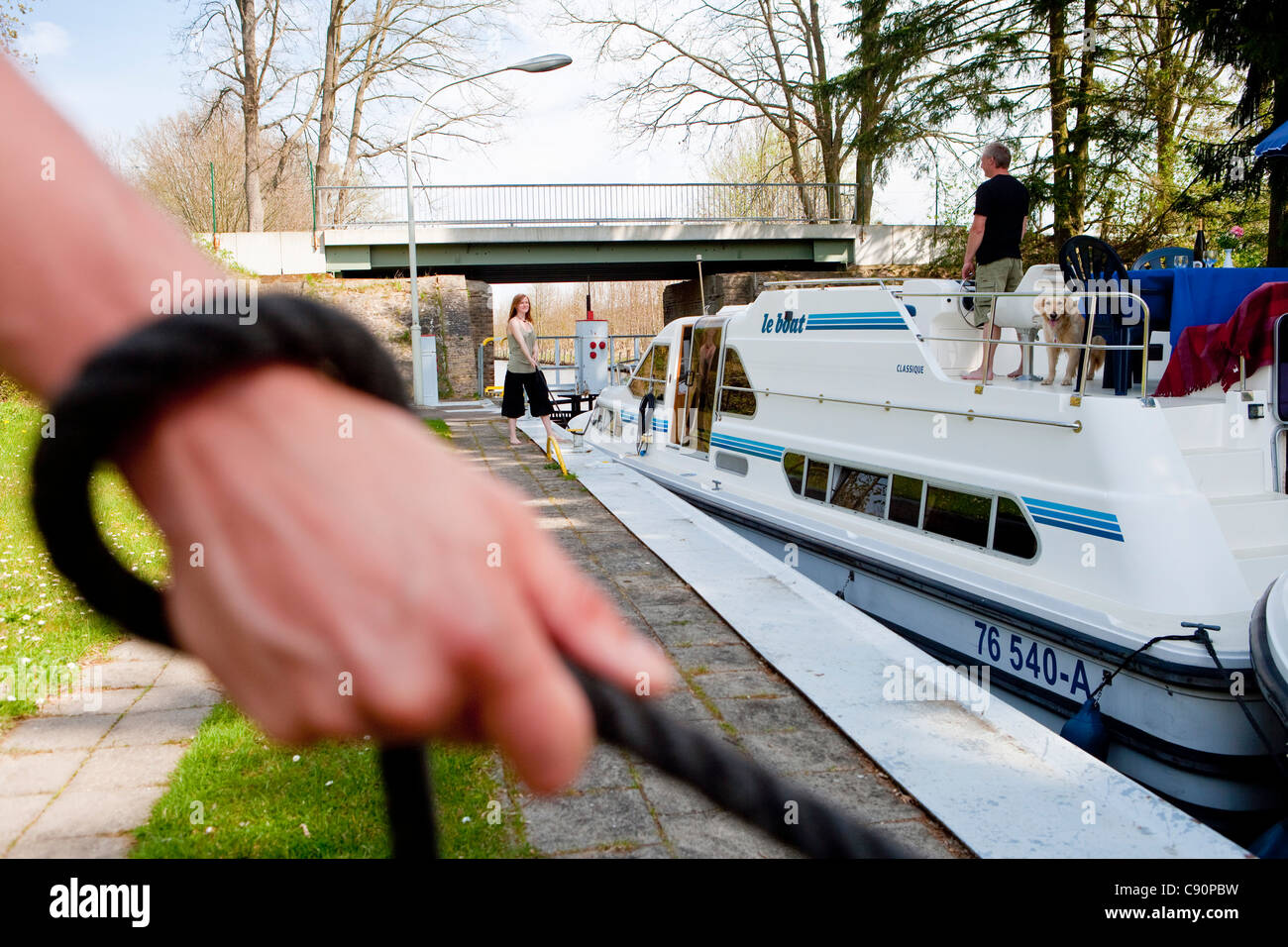 Hand holding a rope to manoeuvre a houseboat through the lock near Zechlinerhuette North Brandenburg Lake District - Stock Image