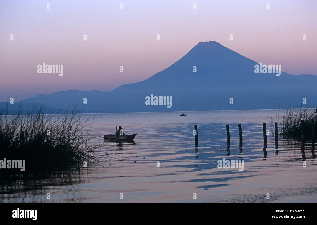 The silhouette of the volcanic cone of Volcan San Pedro towers over the freshwater Lake Atitlan, Guatemala - Stock Image