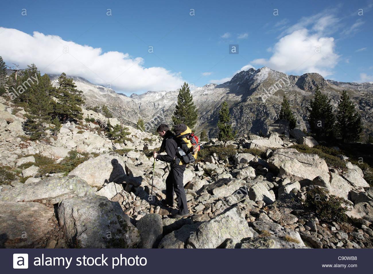 Hiker passing scree, Rundweg Carros de Foc, Nationalpark Aigueestortes i Estany de Sant Maurici, Katalonien, Spanien - Stock Image