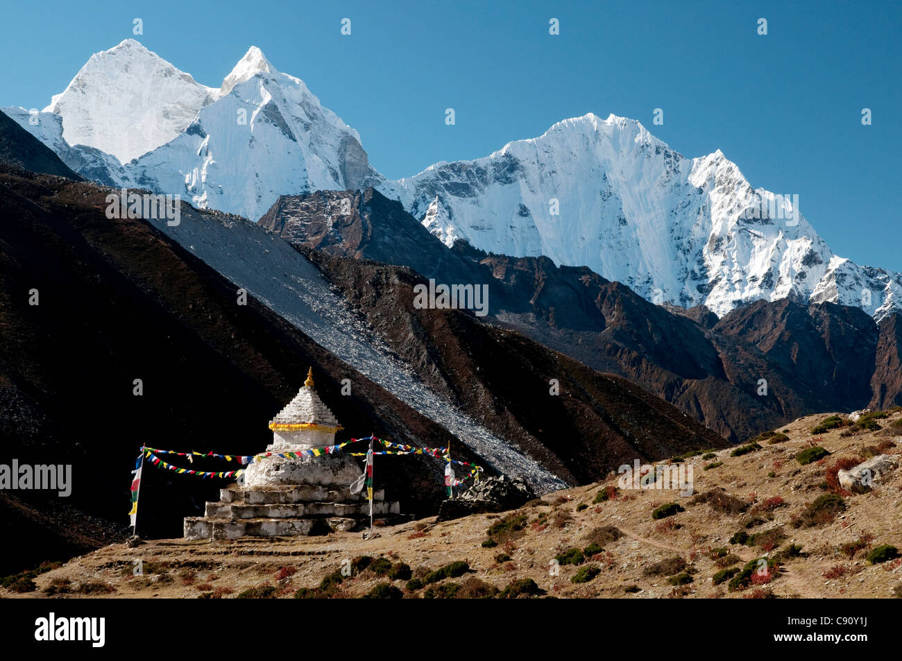 Thamserku and the peak of Kaing Taiga or Kangtega tower over the route to Everest Base Camp in the Solu Khumbu region. - Stock Image