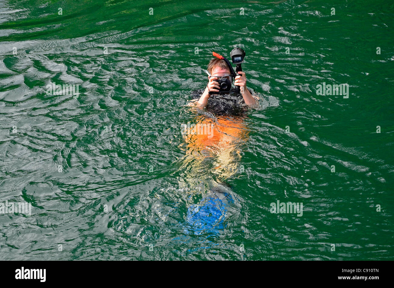 Tourist with underwater camera, Raja Ampat islands near West Papua, Indonesia in the coral triangle, Pacific Ocean. Stock Photo