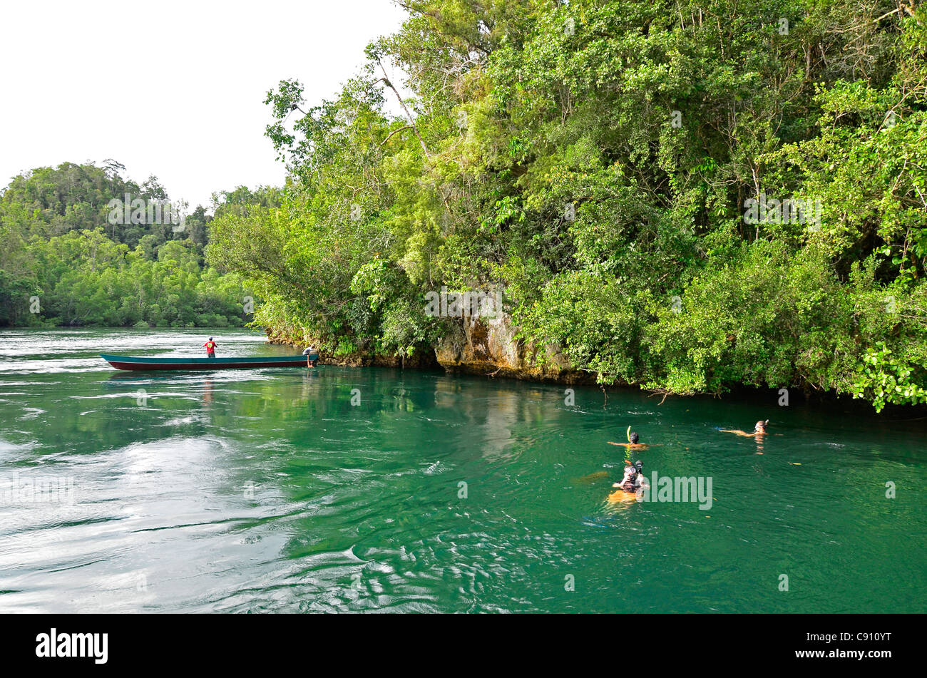 Tourists snorkelling in The Passage, Raja Ampat islands near West Papua, Indonesia in the coral triangle, Pacific Stock Photo