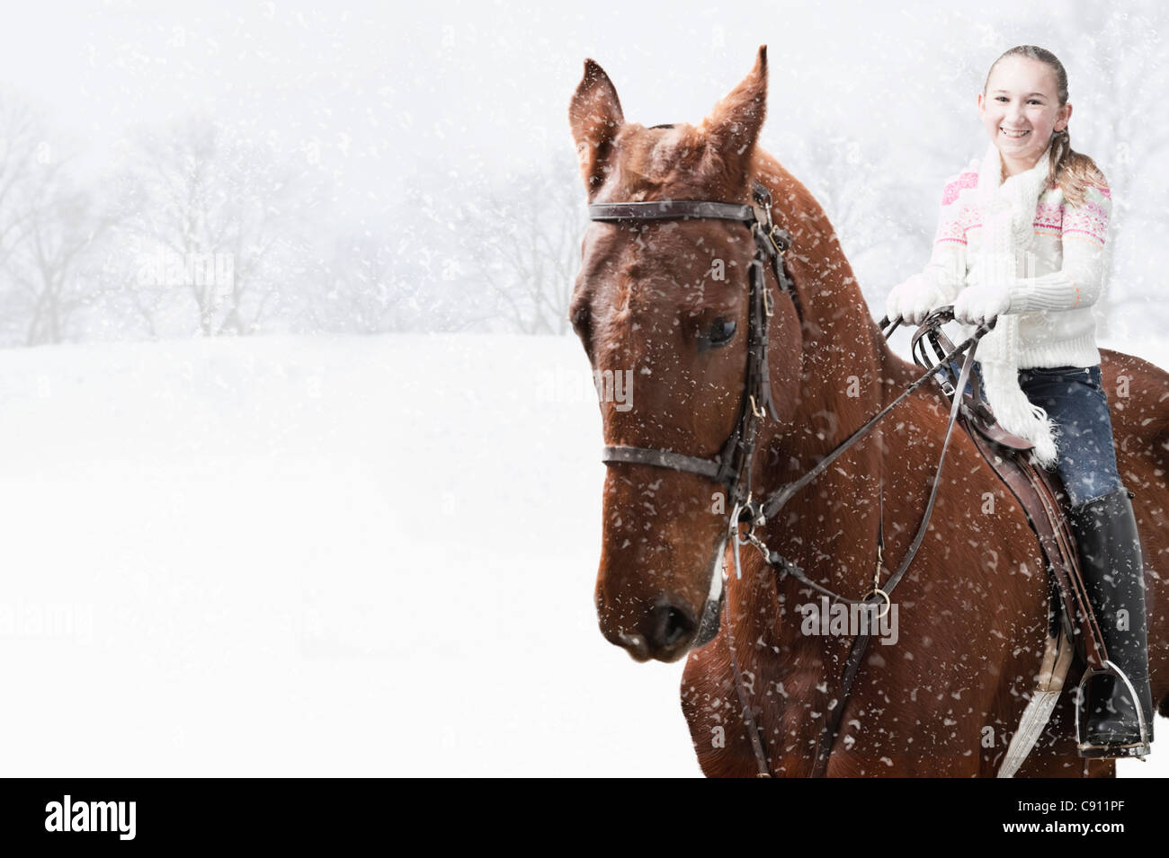 USA, Illinois, Metamora, Smiling girl (10-11) riding horse during winter - Stock Image