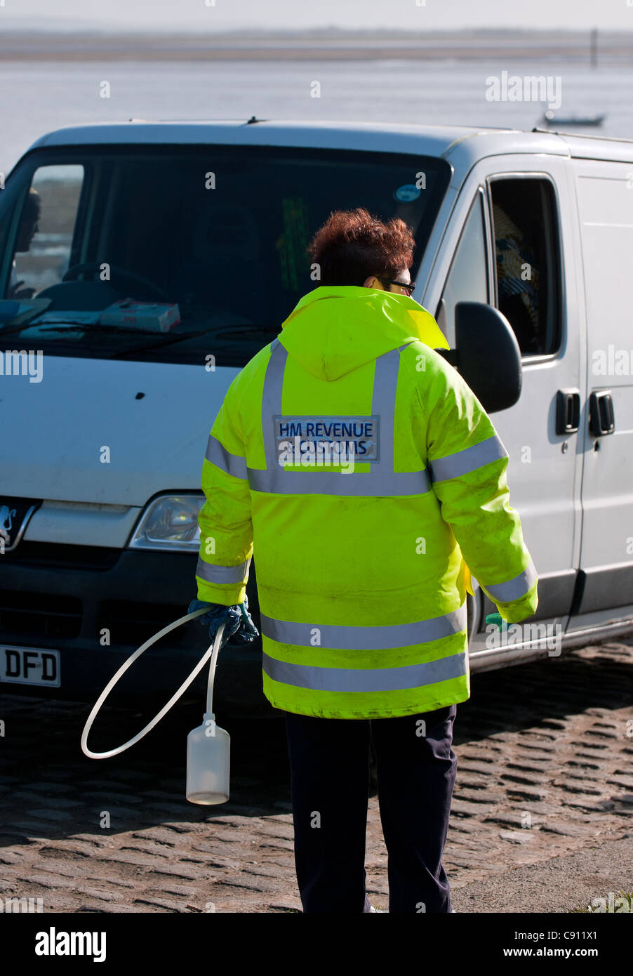 An officer from HM Revenue & Customs checking fuel in a van. - Stock Image
