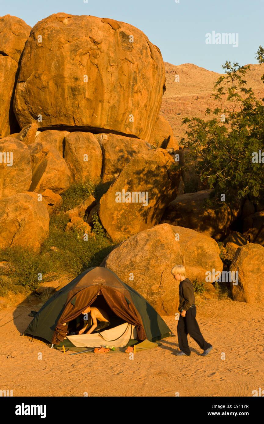 Boys climbing out of their tent on Koiimasis farm Tiras Mountains Namibia - Stock Image