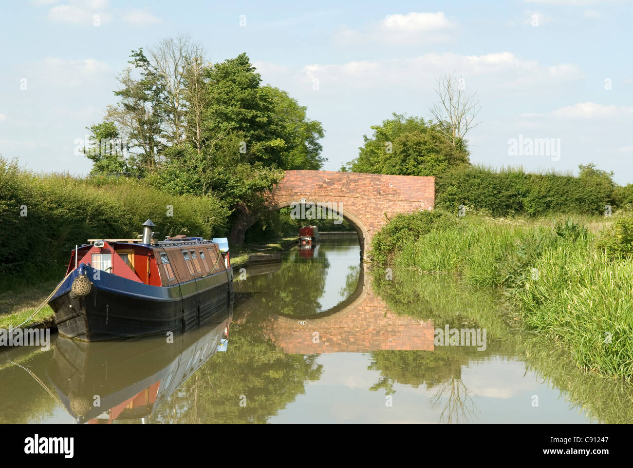 There are many historic small stone bridges and crossings over the canal on the route of the Grand Union Canal which Stock Photo