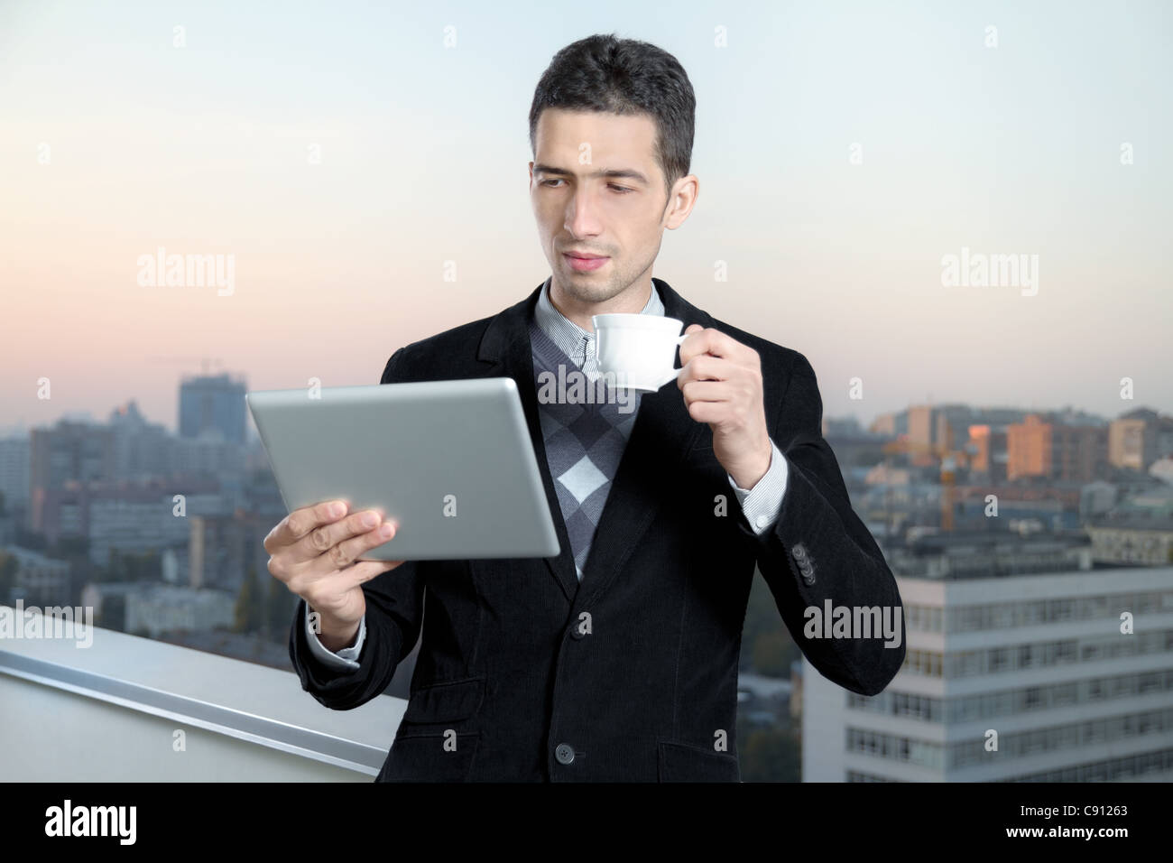 Businessman with a cup of coffee uses a digital tablet on the roof of business center. Stock Photo