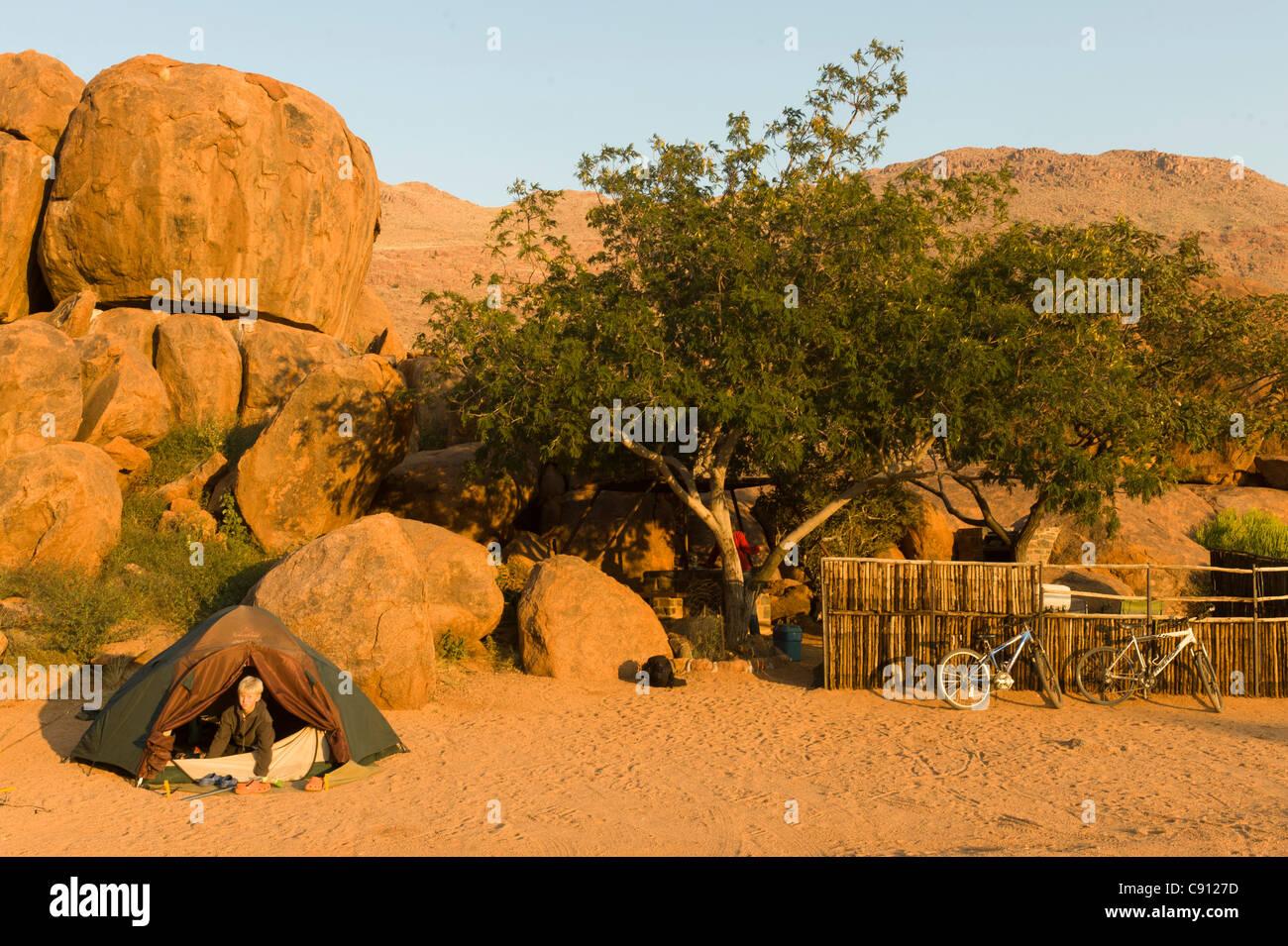 Boy climbing out of his tent on Koiimasis farm Tiras Mountains Namibia - Stock Image
