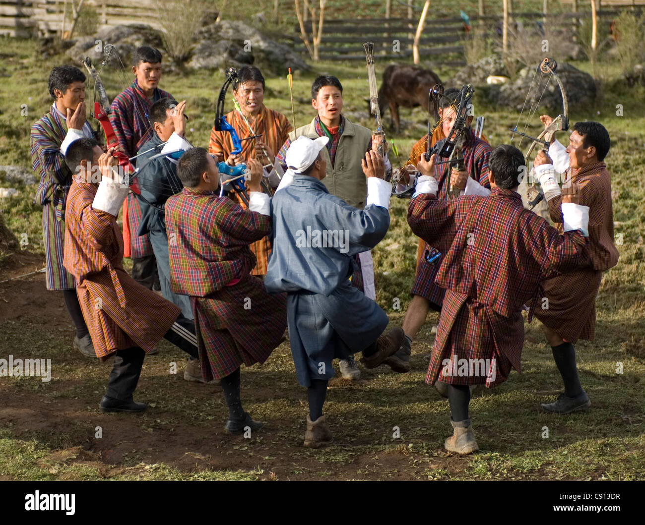 Whenever someone hits the target, the whole team in an inter-village archery contest in Bhutan does a song and dance - Stock Image