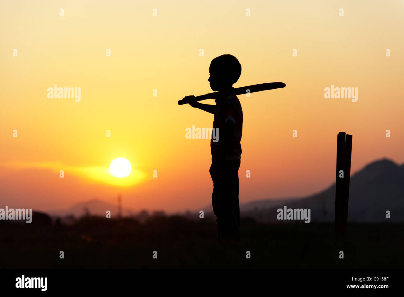 Silhouette of young Indian boy playing cricket against a sunset background - Stock Image