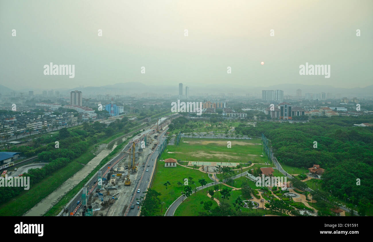 Smoggy sunrise over Kuala Lumpur, Malaysia. Green belt amongst freeways, factories, buildings and pollution - Stock Image
