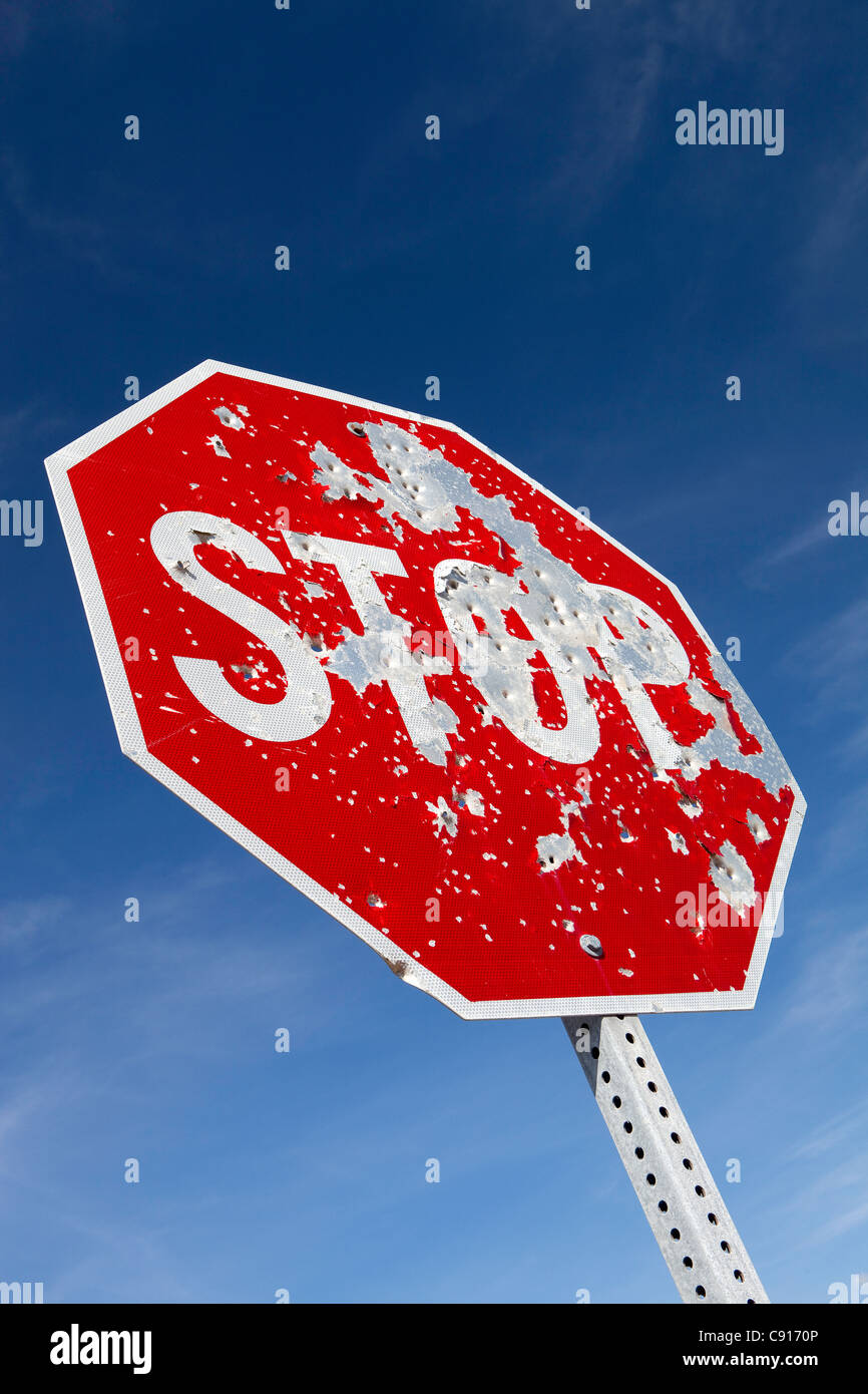 A stop sign on a highway in the American west that is riddled with bullet holes from people shooting it and using Stock Photo