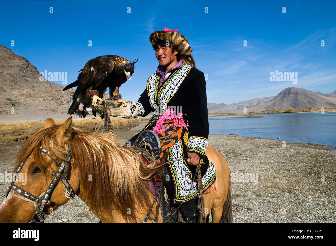 A Kazakh Eagle hunter with his Golden Eagle. - Stock Image