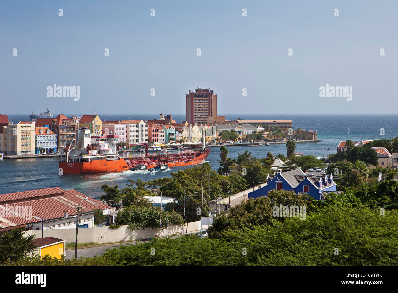 Curacao, Caribbean island, Willemstad. Historic houses on waterfront. Dusk. Chemical products tanker passing Sint - Stock Image