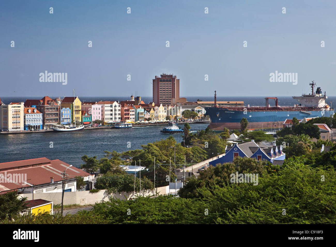 Curacao, Caribbean island, Willemstad. Historic houses on waterfront. Dusk. Oil tanker passing Sint Annabaai. - Stock Image