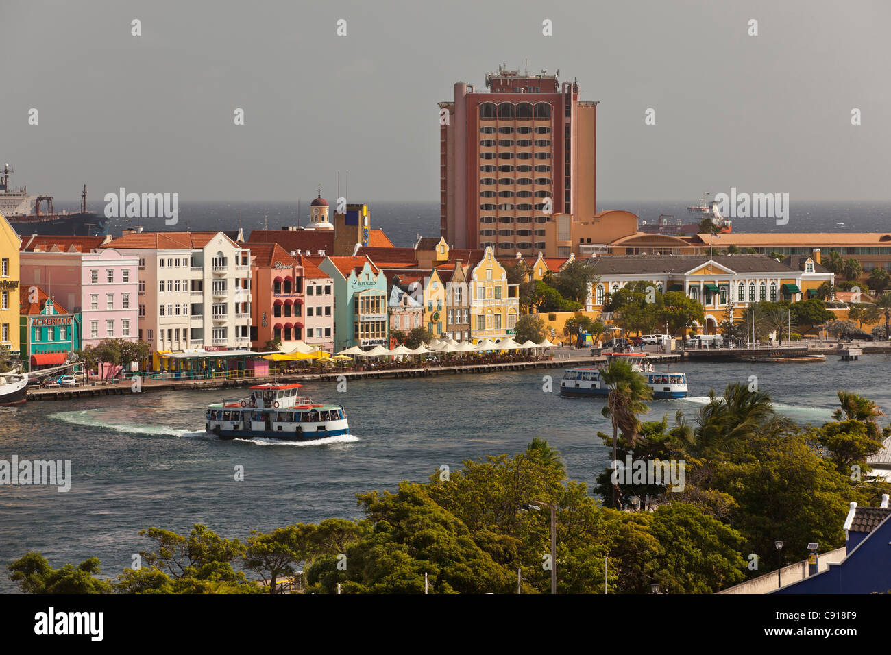 Curacao, Caribbean island, Willemstad. Historic houses on waterfront. Ferry boats crossing St Annabaai. - Stock Image