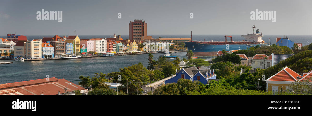 Curacao, Caribbean island, Willemstad. Historic houses on waterfront. Oil tanker and ferry boat crossing St Annabaai. - Stock Image