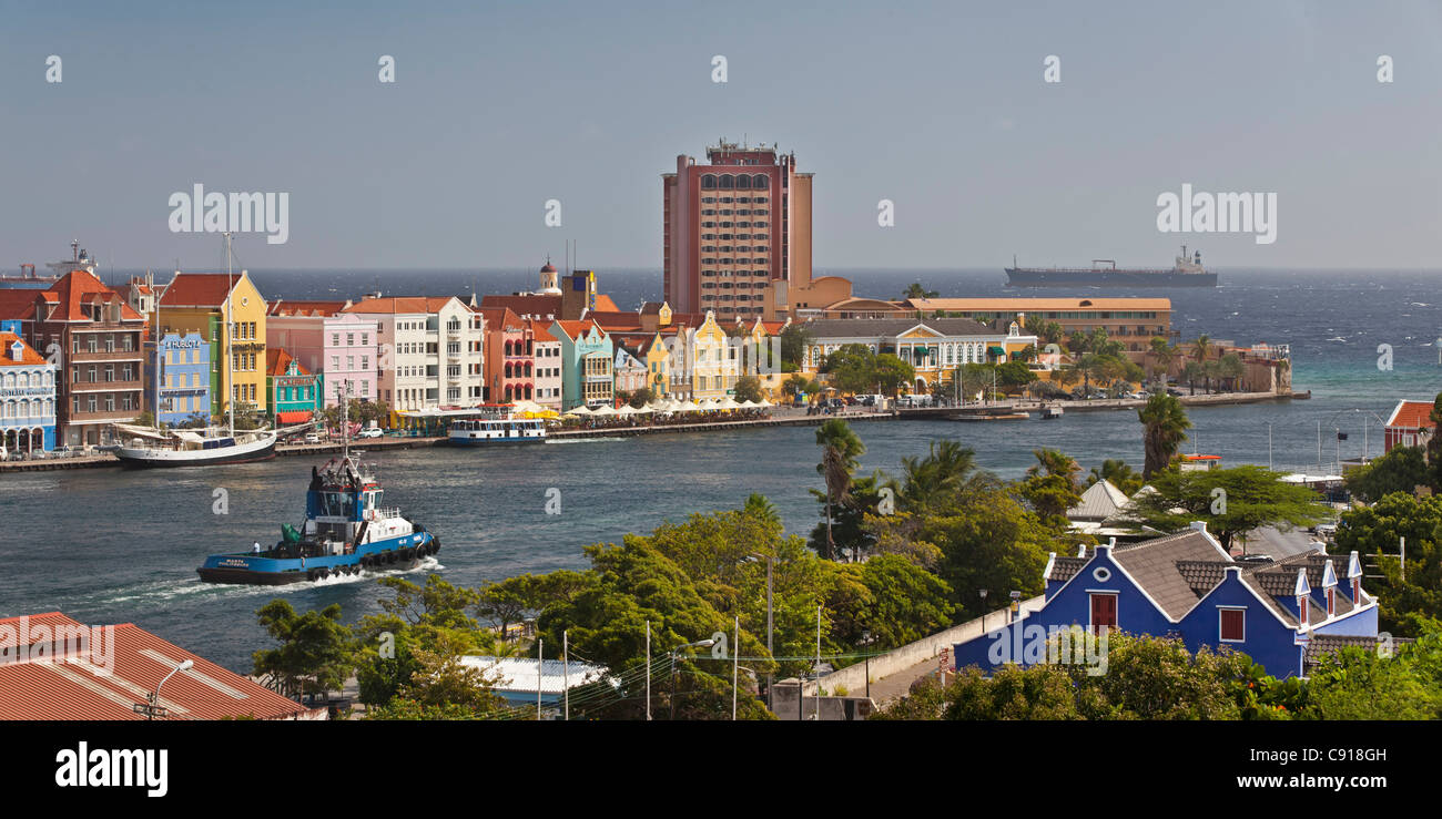 Curacao, Caribbean island, Willemstad. Punda quarter. Historic houses on waterfront. Towboat passing Sint Annabaai. - Stock Image