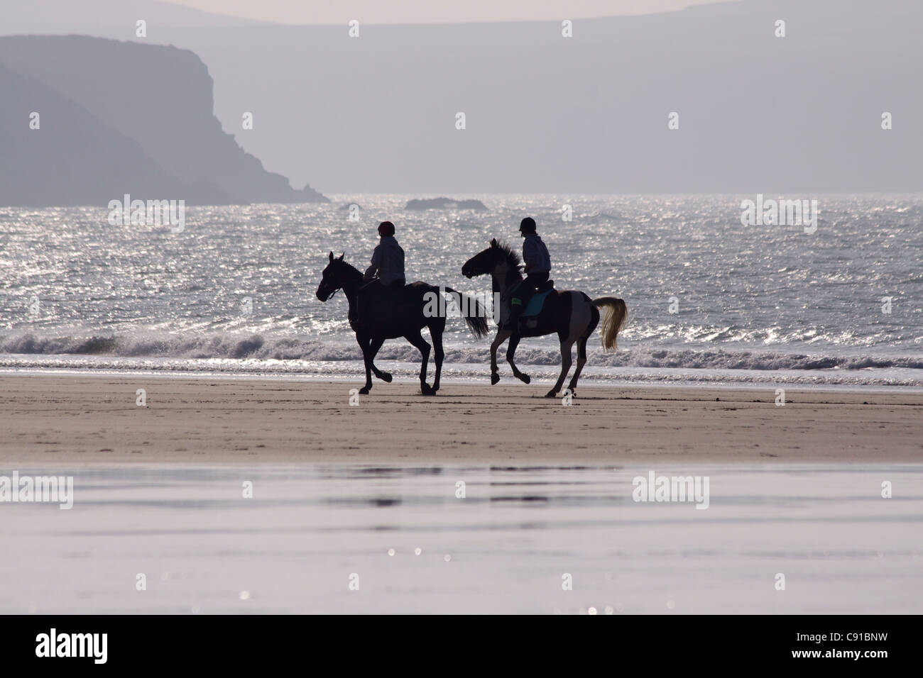 Horse riders often take a ride across Whitesands Bay and the horses benefit from walking on sand. It is a surfing - Stock Image