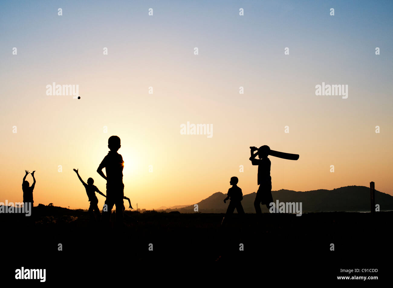 Silhouette of young Indian boys playing cricket against a sunset background - Stock Image