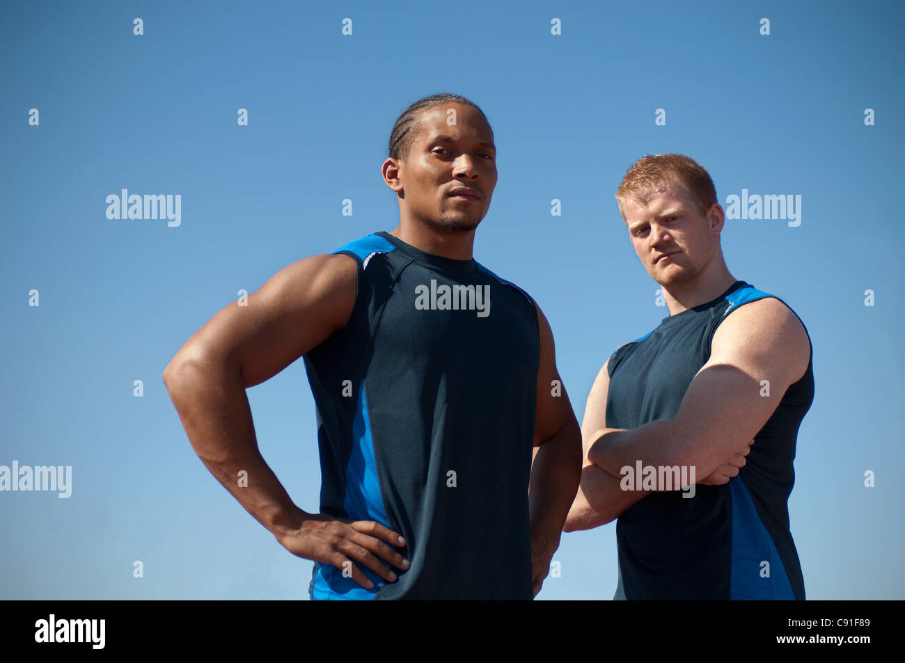 Athlete standing against blue sky - Stock Image